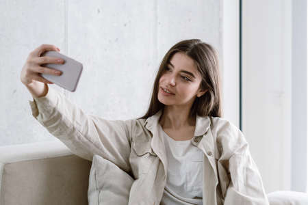 Joyful young woman in a beige shirt sitting on comfort sofa in living room, making self portrait on camera. Millennial girl using her modern smartphone, taking selfie picture and smiling charming
