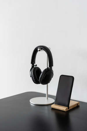 Vertical shot of black wireless headphones on metal stand next to smartphone with blank display at dark table surface against white copy space wall. Modern technologies concept