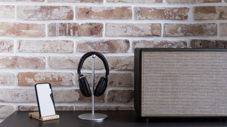 Audio equipment for home entertainment. Music column, smartphone mockup on wooden stand and headphones on table against brick wall