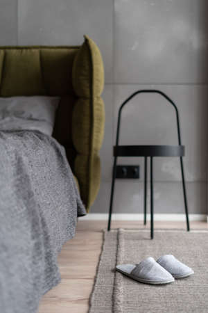 Vertical shot of modern bedroom in minimalistic indoor interior with comfy bed decorated with gray blanket next to industrial metal bedside table on carpeted floor, focus on slippers 免版税图像