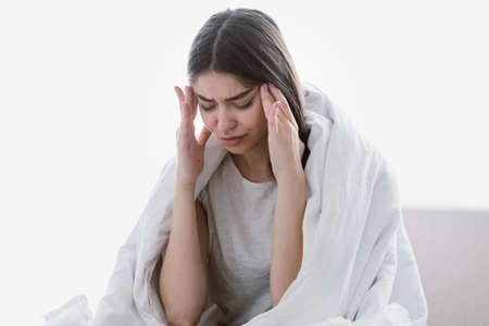 Unhappy exhausted young woman with closed eyes, touching temples, sitting in bed, covered with blanket, tired and suffering from headache or migraine, feeling unwell
