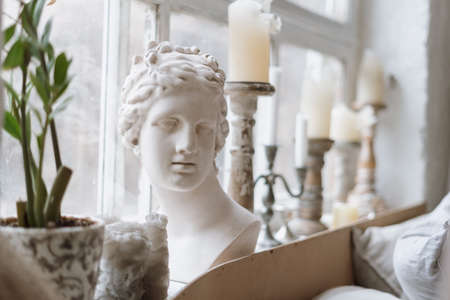 Close up shot of gypsum venus head on windowsill with antique candlesticks and green potted plant, blurred background with light coming from window indoors of cozy bedroom in morning