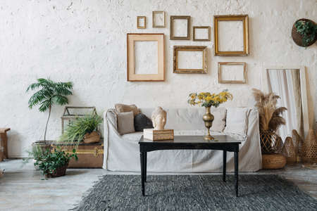 Bohemian style living room decorated with green potted plants. Beige couch, small tea table with Buddha statue and antique metal vase with flowers inside. Empty frames hanging on wall above sofa