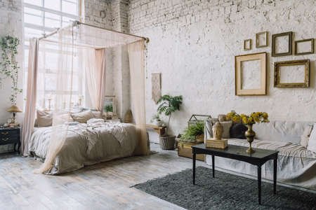 Bed with baldachin and huge window behind it, couch and black table with bust of Buddha and flower vase in Bohemian style room. Gray carpet on wooden floor and brick wall with empty picture frames