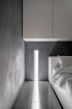 Vertical view of white cupboards hanging on concrete wall over comfortable bed in modern hotel bedroom. Led lighting system and night light in room at modern apartment