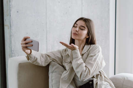 Lovely young woman sitting on couch in living room, making selfie photo on camera, recording video for blog or make online call. Female in casual wear send air kiss, looking at cellphone display