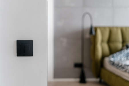 Close up of simple black matte light switch on white wall with bed and metal standing lamp in the blurred background, electrical system in stylish minimalistic loft style bedroom at home