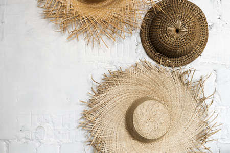Minimalist picture of straw sun hats on white concrete wall indoors, top view. Summer background with copy space for text. Creative design concept 免版税图像