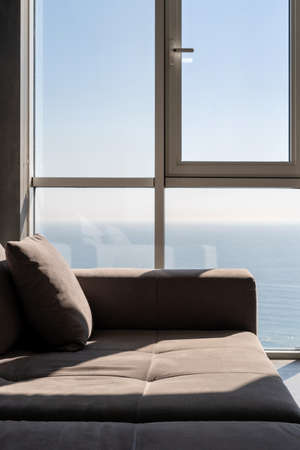 Vertical shot of comfort gray sofa standing against panoramic window in hotel room with sea or ocean view. Couch with cushions in modern apartment with minimalist interior design at living room