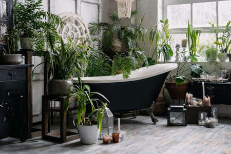 Freestanding bathtub in corner of wide light boho chic bathroom with big window, wooden antique furniture and green potted plants, candles on wooden floor. Bohemian interior design
