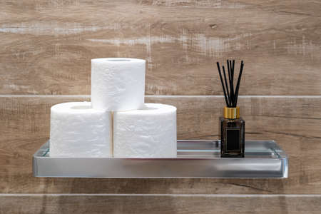 Modern metal chrome shelf with aroma sticks and rolls of toilet paper on wall with wood pattern structure on background. Minimalist interior design in bathroom