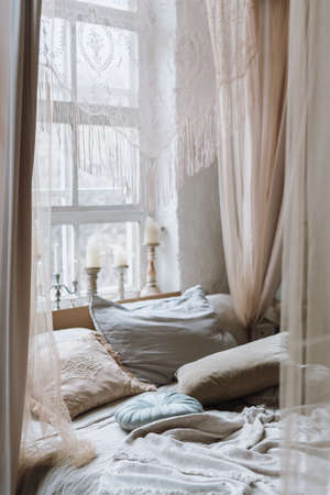 Vertical shot of cozy bed with various pillows and open baldachin, with light coming from big white vintage window with many different candles on windowsill. Empty bedroom in morning 免版税图像