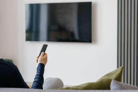 Modern living room interior with blank tv screen panel on blurred white wall background. Cropped shot of woman with remote control in hand sitting on sofa in room with minimalist functional design