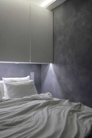 Vertical view of minimalist interior at bedroom with crumpled duvet on comfortable bed, white wardrobe and night light system. Concept of modern furniture for modern house and cozy apartment 免版税图像