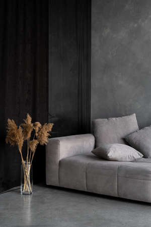 Dry plants in vase standing near gray couch. Vertical view of comfortable ergonomic couch and natural home decor in loft style apartment. Concept of house with modern interior design in living room