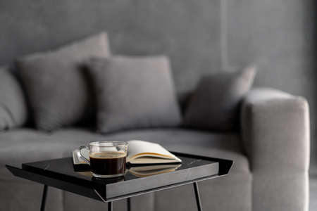 Selective focus on table with cup of coffee and open book against blurred background. Comfortable couch in cozy apartment with modern living room interior. Recreation at home and relaxation concept