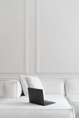Vertical shot of thin black modern laptop on white stylish designer sofa in office relax area or lounge zone with white walls and high ceiling, vertical shot