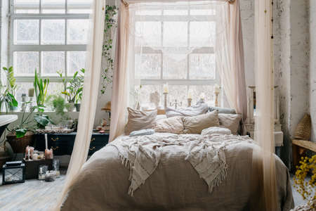 Bohemian style bedroom with comfortable king sized cozy bed with beige curtains and canopy, big white wide windows and candles on windowsill, room decorated with potted greenery and antique furnishing