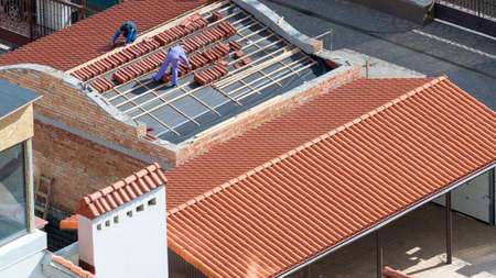 Concept of house, building under construction. High angle view of two professional roofers standing on new roof, install red ceramic tile on wooden frame with protective, waterproof layer at rooftop