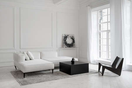 Luxury white leather sofa on legs with cushions on gray carpet in front of window in minimalistic living room in hotel with futuristic chair, abstract picture on wall and decorative vases on table 免版税图像