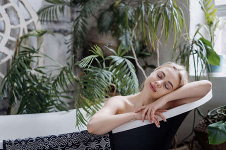Body care, spa and natural beauty concept. Young dreamy woman resting in bathroom, lying in bath at boho chic apartment. Serene lady with closed eyes taking tub against green house plants 免版税图像