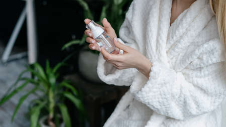 Concept of organic beauty cosmetics. Cropped view of young woman in bathrobe holding bottle with facial cleanser foam in hands, spending morning in bathroom, make skincare procedure 免版税图像
