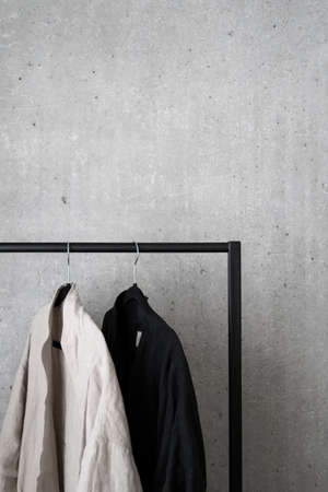 Cropped shot of casual black and white kimono style items of clothing on black metal clothes hanging rail on gray background. Advertising and shopping concept