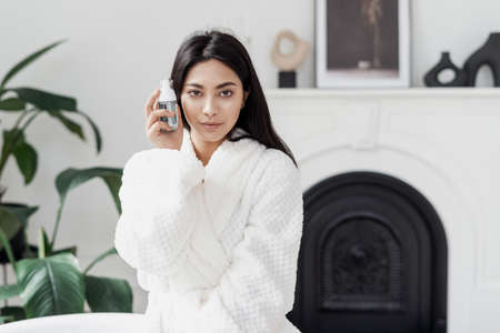 Skincare, beauty and advertising concept. Young asian woman looking at camera, holding bottle with skin care cosmetic near pure and perfect face. Female in white bathrobe spending morning in bathroom Standard-Bild