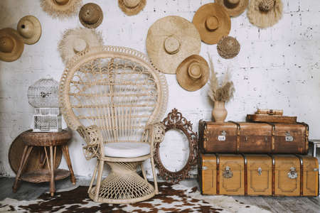 Vintage room with straw chair and antique mirror frame next to it on cow skin carpet, compact woven table with small white stylish bird cage, couple of vintage chests and straw hats on brick wall Standard-Bild