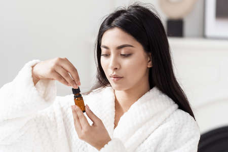 Portrait of young asian model wearing white bathrobe holding and opening skincare product in glass bottle with pipette. Beautiful woman using organic cosmetics for health and wellbeing