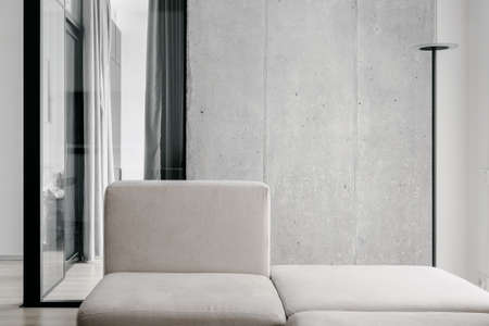 White stylish couch and contemporary standing lamp in space with modern minimalistic design, room behind sofa having glass walls with curtains used for privacy