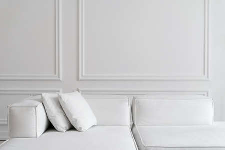 Stylish contemporary designer white sofa with two cushions in room with white walls and high ceiling, sun rays shining through window, cropped shot. Minimalistic design concept