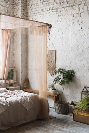 Vertical shot of Bohemian style bedroom with tall ceiling, big bed with baldachin and small cabinet with mirror next to it, wooden furniture with green potted plants and ornament hanging on brick wall Standard-Bild