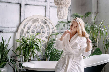 Beauty treatment concept. Smiling and dreamy young woman in bathrobe sitting on freestanding bath, perform daily hair care routine. Boho chic bathroom with green house plants in room