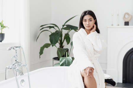 Beautiful young asian woman sitting in light spacious bathroom with green plants wearing white bathrobe preparing for pampering morning routine. Beauty and selfcare concept