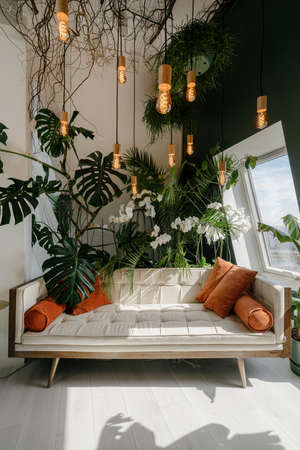 Vertical shot of light cozy boho style living room with modern beige sofa and orange pillows in relaxing area, decorated with different green plants Standard-Bild