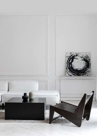 Vertical shot of stylish white comfy leather sofa in empty lounge zone with black futuristic chair and tea table with two modern vases, room decorated with black and white abstract picture