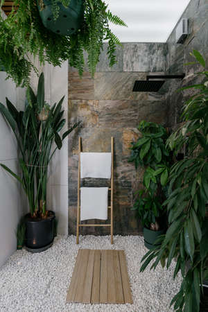 Shower cabin with wooden hanger for fresh and clean towel in modern apartment. Vertical shot of tropical bathroom with brown marble tiles on walls, pebble floor, and different green plants Standard-Bild
