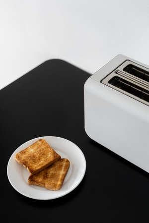Tasty breakfast. Vertical shot of toasted bread on plate and modern white two slice toaster on black table, blurred background Stock Photo