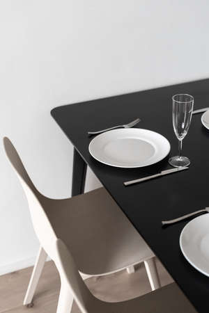 Vertical shot of black matt kitchen table with dinner set up, view from above. White dinnerware, wineglasses and cutlery in minimalistic black and white interior design Stock Photo