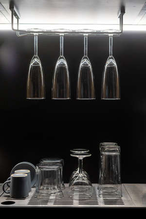 Vertical shot of clean washed and polished wine glasses hanging above empty water cups and tea set drying after washing on kitchen countertop. Dishware concept