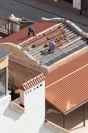 Building industry, improvement and reconstruction concept. New shingle on construction site, vertical shot. High angle view of professional workers on rooftop install ceramic tile on wooden frame