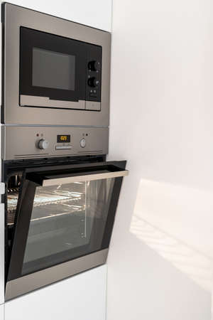 Vertical shot of steel microwave and slightly open oven with light lit, time display and couple control knobs in modern white hi tek kitchen Stock Photo
