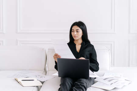 Beautiful young female accountant sitting on sofa with bunch of paperwork, looking at document analyzing sales and income while sitting on sofa and using laptop. Asian woman freelancer working at home