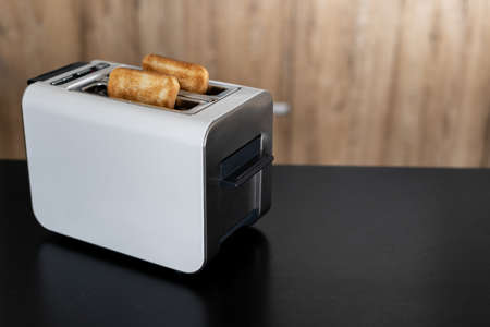 Breakfast ready to eat. White electrical two slice toaster with with popped up toasted bread inside, modern kitchen appliance on black counter with blurred wooden background