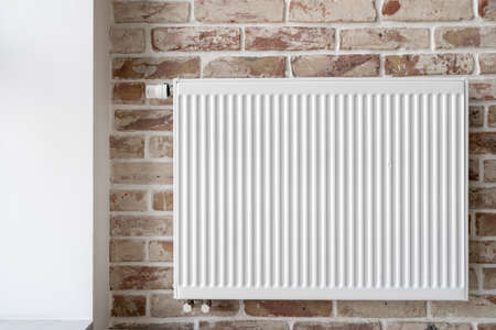 Close up shot of central heating system radiator with thermostat on brick wall in loft style interior in contemporary apartment. Electric consumption efficiency in house