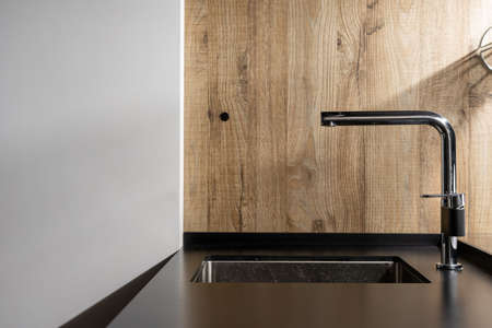 Stylish built in black colored sink with chrome faucet in stylish kitchen with matte countertop against wall with wooden pattern structure in minimalist home interior