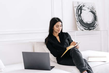 Beautiful young female freelance writing information in notebook while sitting on sofa at home and listening online webinar on laptop. Businesswoman working on business plan at remote home office