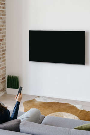 Vertical cropped shot of woman watching TV mounted on white wall, sitting on couch with remote in hand and select channel on television while relaxing in modern cozy living room