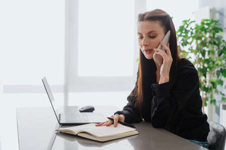 Freelance concept and remote work. Successful busy woman talking on modern smartphone, looking at notepad. Young businesswoman sitting behind table in home office checking schedule for new appointment